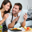 Couple in home kitchen using electronic tablet — Stock Photo