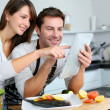 Couple in home kitchen using electronic tablet — Foto Stock