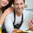 Couple in home kitchen using electronic tablet — 图库照片