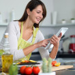 Woman in kitchen looking for dish recipe on internet — Stock Photo #13962095