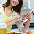 Woman in kitchen looking for dish recipe on internet — Stock Photo #13962104