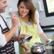 Man preparing dinner and making her wife taste the food — Stock Photo #13962119