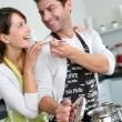 Man preparing dinner and making her wife taste the food — Stock Photo #13962120