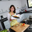Womin kitchen holding fish dish — Stock Photo #13962140