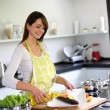 Woman in kitchen preparing pasta dish - Stock Photo