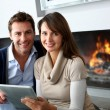Stock Photo: Couple sitting by fireplace and websurfing with tablet