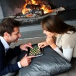 pareja sentada por la chimenea y websurfing con Tablet PC — Foto de Stock