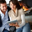 Couple sitting by fireplace and websurfing with tablet — Foto Stock