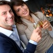 Cheerful couple drinking champaign by fireplace — Stock Photo