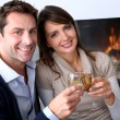 Cheerful couple drinking champaign by fireplace — Stock Photo #13962226