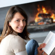 Portrait of beautiful womreading book by fireplace — Stock Photo #13962247