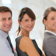 Cheerful business team standing in hallway - Stock Photo