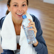 Girl sitting in gym with bottle of water — Stock Photo #13962967