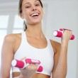 Fitness girl lifting dumbbells in gym — Stock Photo #13963018