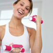 Fitness girl lifting dumbbells in gym — Stock Photo #13963022