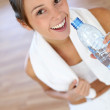 Cheerful fitness girl drinking water after exercising — Stock Photo #13963041