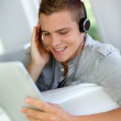 Young man listening to music with digital tablet — Stock Photo #13964189