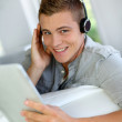 Young man listening to music with digital tablet — Stock Photo #13964190