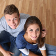 Upper view of young couple sitting on the floor — Foto Stock