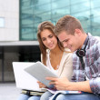 Students using tablet outside university building — Stock Photo #13964415
