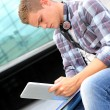 University student using digital tablet and headphones — Stock Photo #13964425