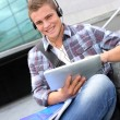 College student using digital tablet and headphones — Стоковая фотография