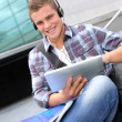 College student using digital tablet and headphones — Stock fotografie
