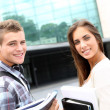 Young couple standing outside university campus — Stock Photo #13964464
