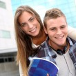 Young guy giving piggyback ride to girlfriend — Stock Photo