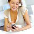 Young woman sending short message with telephone — Stock Photo