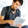 Royalty-Free Stock Photo: Handsome guy listening to music on internet with tablet