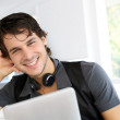 Handsome guy listening to music on internet with tablet — Stock Photo