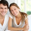 Photo: Portrait of smiling young couple at home