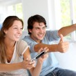 Young couple playing video games at home — ストック写真