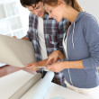 Couple looking for the best colour of wallpaper — Stock Photo #13964944