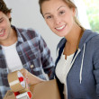 Smiling young woman packing boxes to move out - Stock Photo