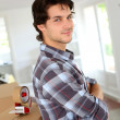 Young man packing boxes to move in new flat — Stockfoto