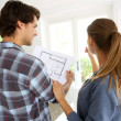 New property owners looking at home blueprint — Stock Photo
