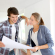 Stock Photo: New property owners looking at home blueprint
