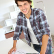 Cheerful young man looking at colours sample for new home — Stock Photo #13964982