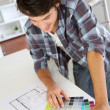 Cheerful young man looking at colours sample for new home — Stock Photo