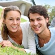 Cheerful couple of lovers laying in garden — Stock Photo #13965021