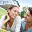 Cheerful couple of lovers laying in garden — Stock Photo #13965029