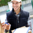 Portrait of smiling delivery man - Stockfoto
