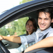 Cheerful couple driving car - Stock Photo