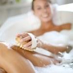 kobieta w wannie szorowanie jej nogi — Zdjęcie stockowe