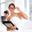 Businesswoman with eyeglasses standing in offices — Stock Photo #13965265