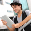 Royalty-Free Stock Photo: Trendy student standing outside with digital tablet