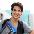 Cheerful student standing outside college building — Stock Photo #13965464