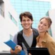 Cheerful couple of students standing on college campus — Stock Photo